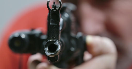 Extreme close-up of gunpoint of hunting gun with laser sight. Blurred Caucasian Live Action