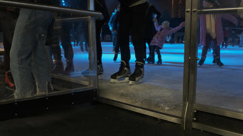 Legs close-up, people go to the ice rink. Girls and boys on ice skates. Public Live Action