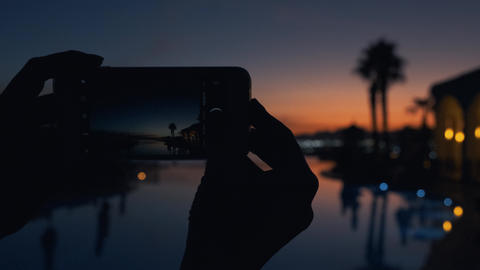 Young woman taking photos of the sunset at luxury tropical resort. Girl at dusk Live Action