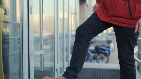 Weird way to open the door. Man opening office door with leg. Entering to the Live Action