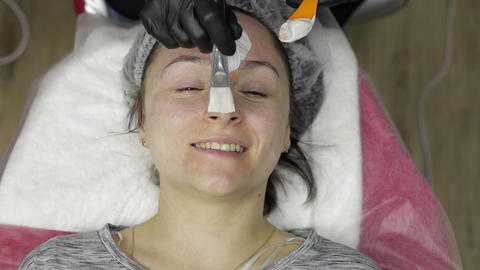Cosmetologist applying moisturizing cream mask using brush on woman client face Live Action