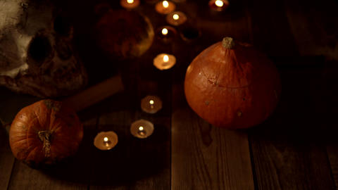 Still life of pumpkins and skulls on a wooden table when the candles go out Live Action