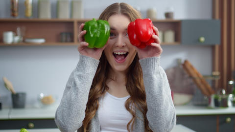 Portrait of young woman changing emotions with colorful peppers at home kitchen Live Action