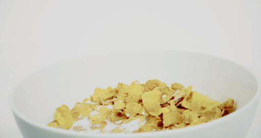 cereal corn flakes in a bowl pouring with milk on white background, concept of diet Live Action