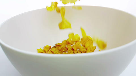 cereal corn flakes falling down in a bowl, shot in slow motion on white background, concept of diet Live Action