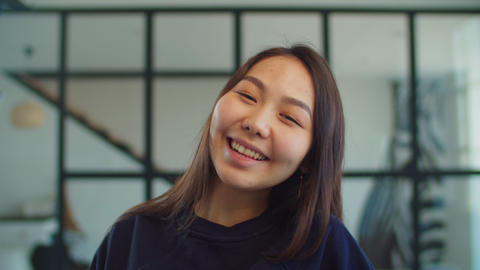 Joyful adorable young asian woman smiling indoors Live Action
