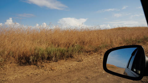 Passenger car driving along a country road among beautiful deserted field in Live Action