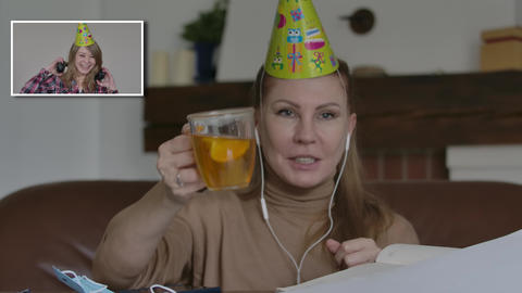 Two joyful Caucasian women in party hats celebrating in video chat. Positive Live Action