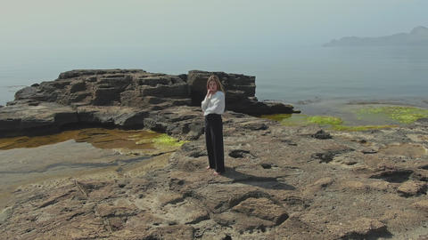 A young woman in trousers and a white blouse stands barefoot on a rocky GIF