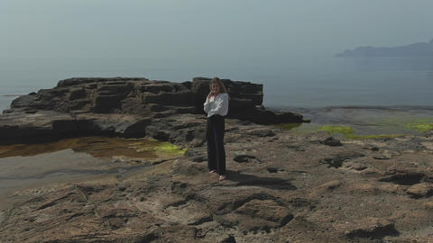 Aerial filming of a young woman with her feet stands on a rocky sea shore Live Action