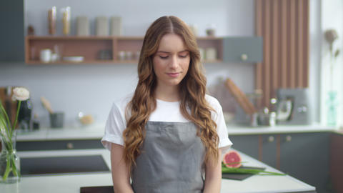 Young woman smiling camera in kitchen. Beautiful housewife posing camera home Live Action
