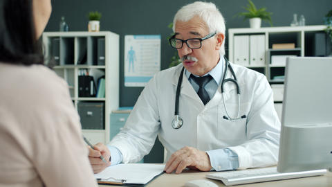 Friendly senior doctor talking to female patient during appointment in clinic Live Action
