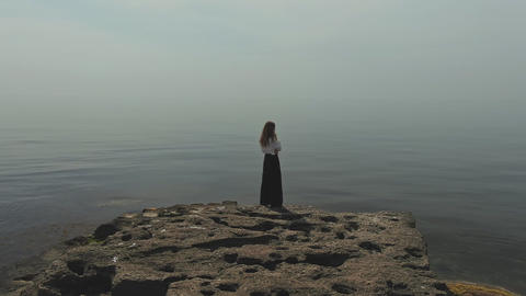 Aerial footage of a young woman standing on a stone by the sea hair flutters in Live Action