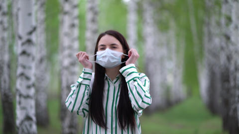 Young woman takes off medical mask and takes a deep breath in the birch grove Live Action
