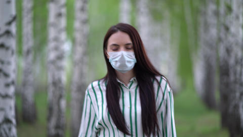 young girl in a protective mask walks in a birch grove Live Action