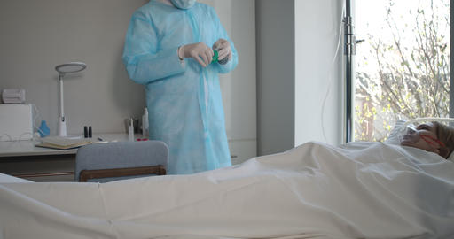 Man in face mask and protective gloves taking care of Covid-19 positive patient Live Action