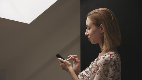 Young woman in profile works on smartphone Live Action