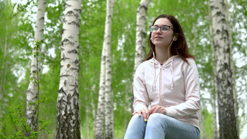 A young woman sits in nature with headphones in her ears. A girl sits on a stump Live Action