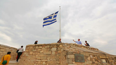 Greek flag on top of ancient Acropolis, tourists taking photos, debt crisis Footage