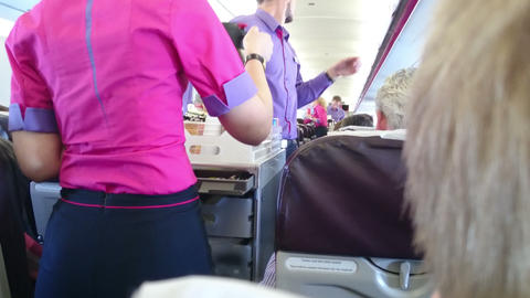 Woman in flight attendant uniform pouring coffee for passenger on board of plane Footage