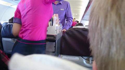 Stewardess serving coffee to passenger during flight. Transportation services Footage