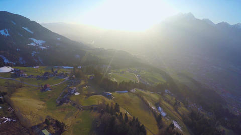 Aerial shot of small farming village on green hill of mountain in rays of sunset Live Action