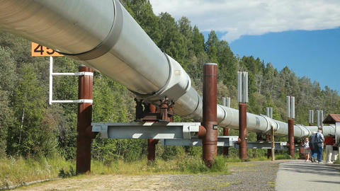 Alaska oil pipeline men walking under flow of oil to terminal P HD 7946 Live Action