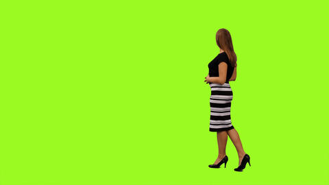 Back view of an elegant young woman walking & watching something Footage