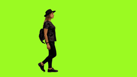 Side view of young woman in leather jacket walking, alpha channel Live Action