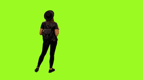 Back view of young female walking & watching something, alpha channel Footage
