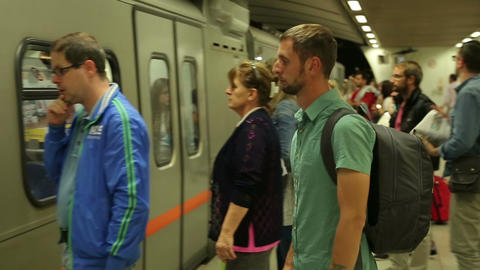 Many people on subway, automatic doors of train open, passengers entering car Footage