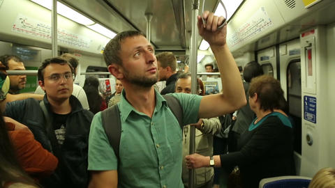 Young man with rucksack on back traveling by metro train, checking subway map Footage