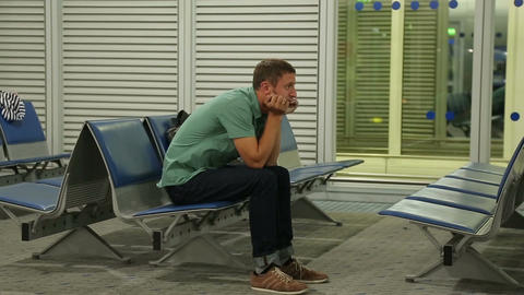 Unhappy male passenger sitting at waiting room, flight canceled or delayed Footage
