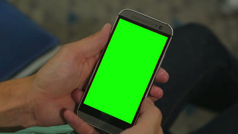 Closeup of male hands holding smart phone with green screen prekeyed for effects Footage