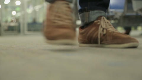 Male legs wearing training shoes walking in public place, footsteps of people Footage