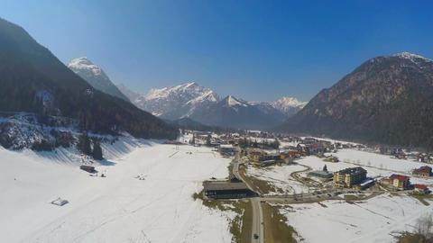 Beautiful winter landscape, peaceful resort town in mountains below blue sky Footage