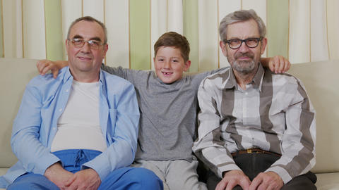 Two grandfathers with a grandson on a sofa Live Action