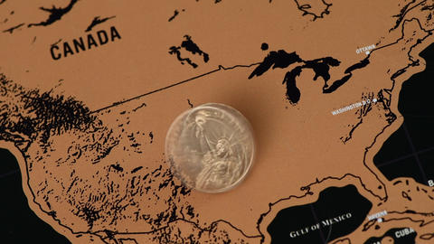 one dollar coin on black scratch travel map of United States of America Live Action