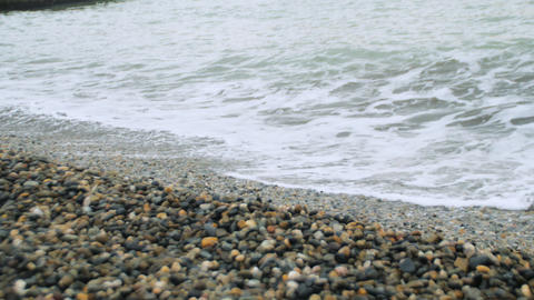 Waves on the shore of a pebble beach at sea (Medium Shot) Live Action