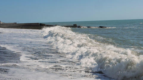 Waves beat on the shore in slow motion (Medium Shot) Live Action