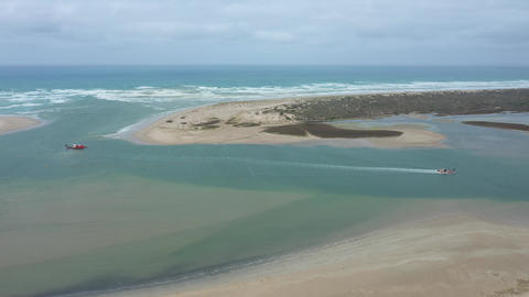Aerial footage of a sand dredger returning to port at the mouth of the River Murray in regional Live Action