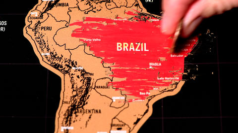 Person erase Brazil with one dollar coin on black scratch travel map ライブ動画