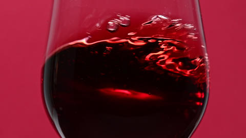 Close up swirling red wine in wineglass over red Live Action