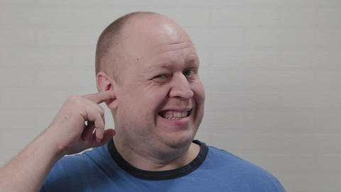 A bald man picks his ear with his finger at the camera. Portrait of a bald man Live Action