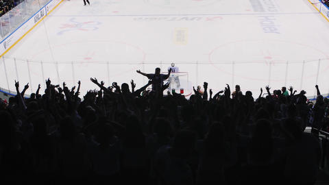 sports fans clap hands with leader to support hockey team Live Action