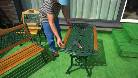 Skilled worker repair renew vintage table furniture in house yard Live Action
