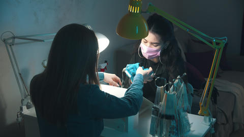 Manicure master in mask and gloves doing manicure - cleans the cuticle using Live Action