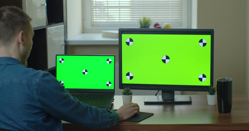 Creative Designer Sitting at His Desk Uses Desktop Computer with Two Green Mock Live Action