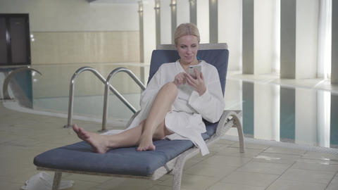 Wide shot of blond smiling Caucasian woman lying on sunbed in spa hotel and Live Action