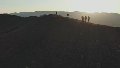 aerial filming of a group of tourists walks up the hill in the sunset GIF